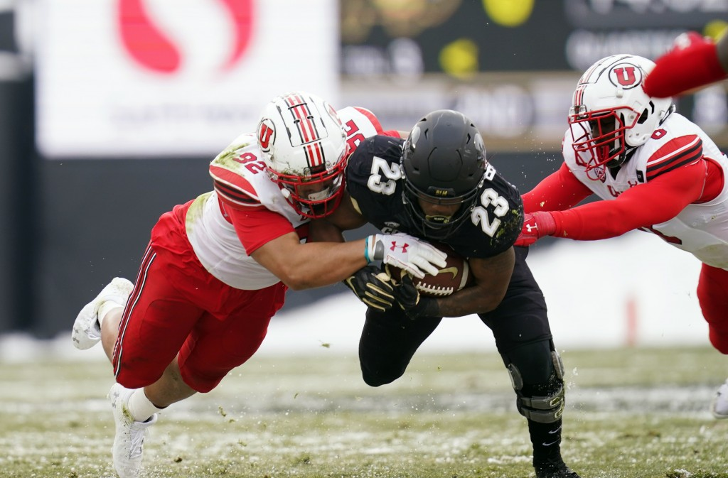 Colorado running back Jarek Broussard, center, is stopped after a short gain by Utah defensive end Maxs Tupai, left, and linebacker Devin Lloyd in the...