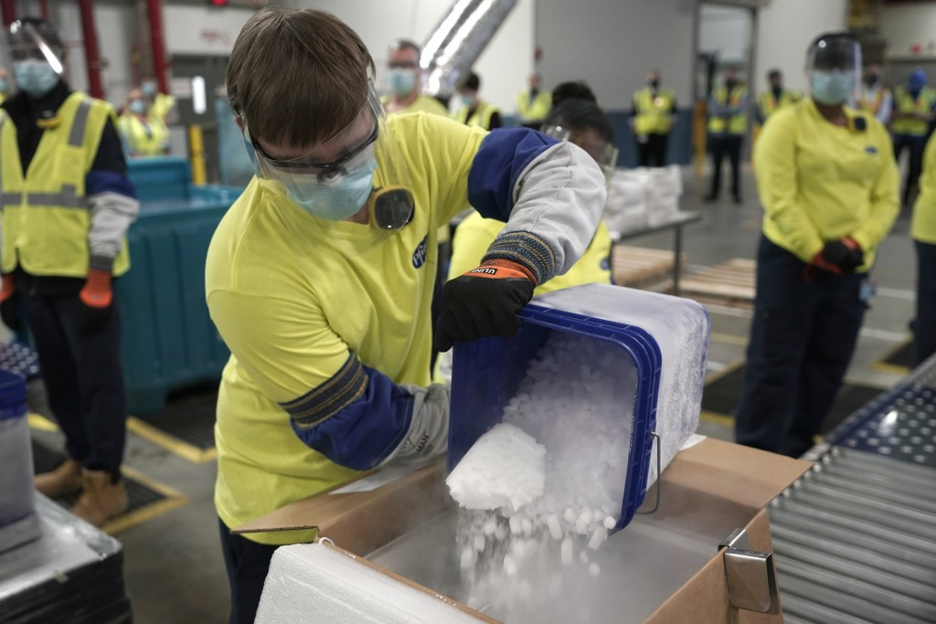 Dry ice is poured into a box containing the Pfizer-BioNTech COVID-19 vaccine as it is prepared to be shipped at the Pfizer Global Supply Kalamazoo man...