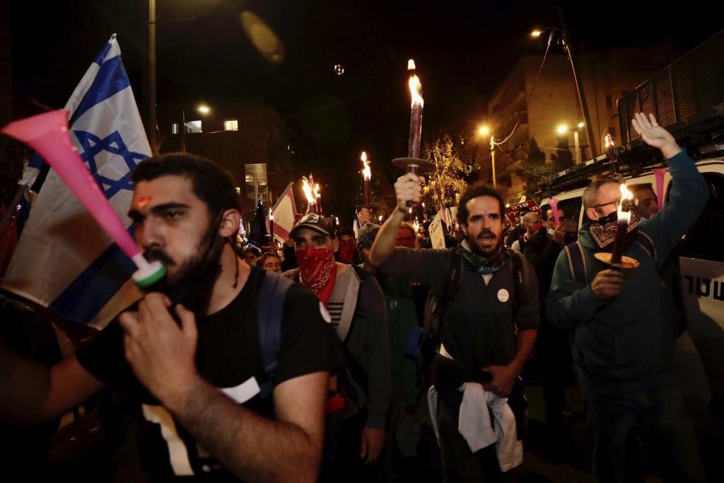 Israeli protesters chant slogans during a demonstration against Israeli Prime Minister Benjamin Netanyahu in Jerusalem, Saturday, Dec. 12, 2020. (AP P...