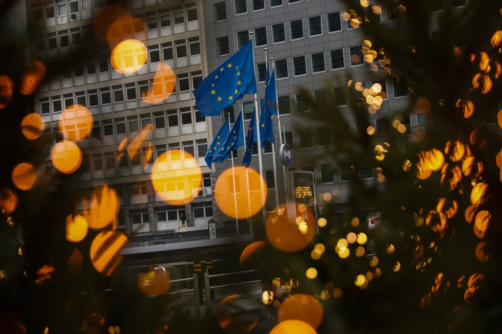 European Union flags, seen through Christmas decoration lights, flutter in the wind outside the European Commission headquarters in Brussels, Saturday...