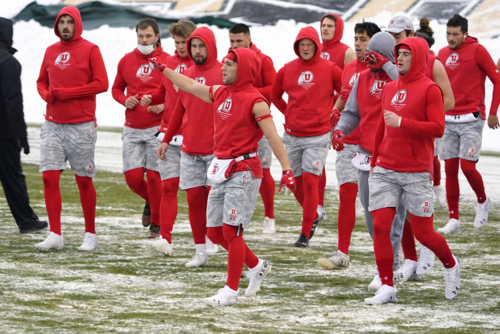 Utah wide receiver Britain Covey, center, raises his arm as he warms up with teammates in sub-freezing temperatures and light snow before the first ha...