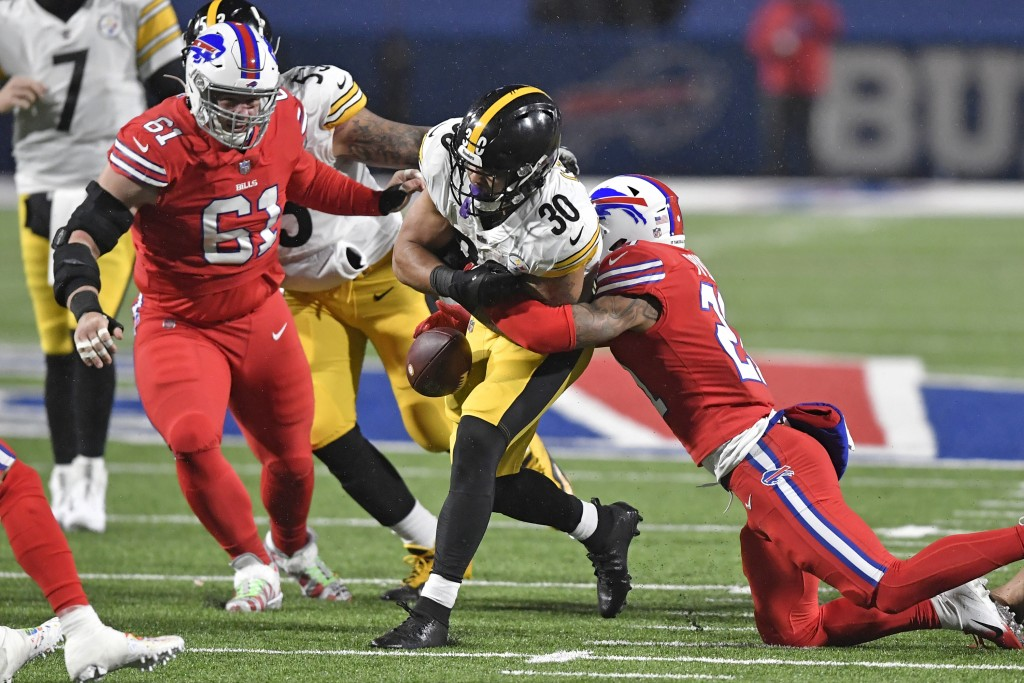 Buffalo Bills free safety Jordan Poyer, right, forces a fumble by Pittsburgh Steelers running back James Conner (30) during the first half of an NFL f...