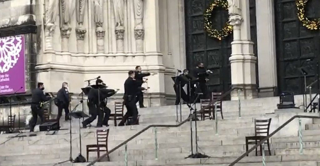 New York police officers move in on the scene of a shooting at the Cathedral Church of St. John the Divine, Sunday, Dec. 13, 2020, in New York. A man ...