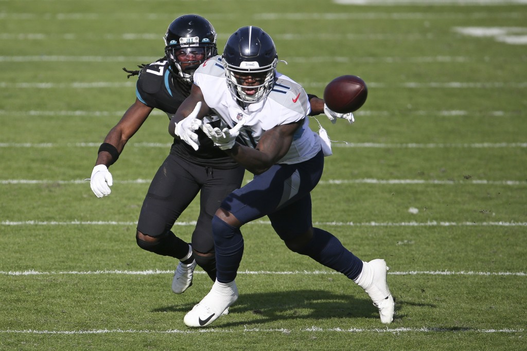 Tennessee Titans wide receiver A.J. Brown, right, makes a reception in front of Jacksonville Jaguars cornerback Tre Herndon (37) during the second hal...