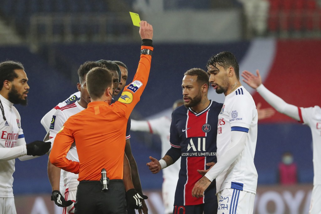 Referee Benoit Bastien shows a yellow card to PSG's Neymar, center, during the League One soccer match between Paris Saint Germain and Lyon, at the Pa...