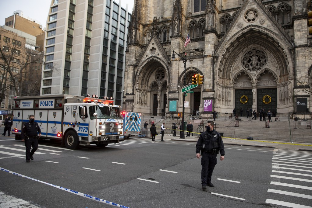 New York police officers block off the scene of a shooting at the Cathedral Church of St. John the Divine, Sunday, Dec. 13, 2020, in New York. A man w...