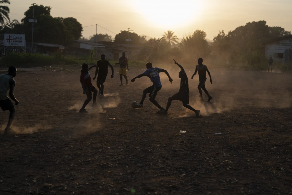 Youths play soccer during as the sun sets in Koidu, district of Kono, Sierra Leone, Tuesday, Nov. 24, 2020. (AP Photo/Leo Correa)