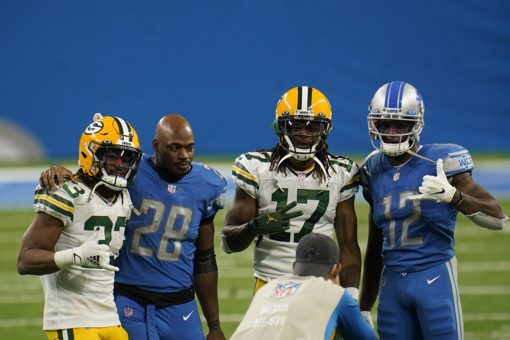 From left, Green Bay Packers running back Aaron Jones (33), Detroit Lions running back Adrian Peterson (28), Packers wide receiver Davante Adams (17) ...