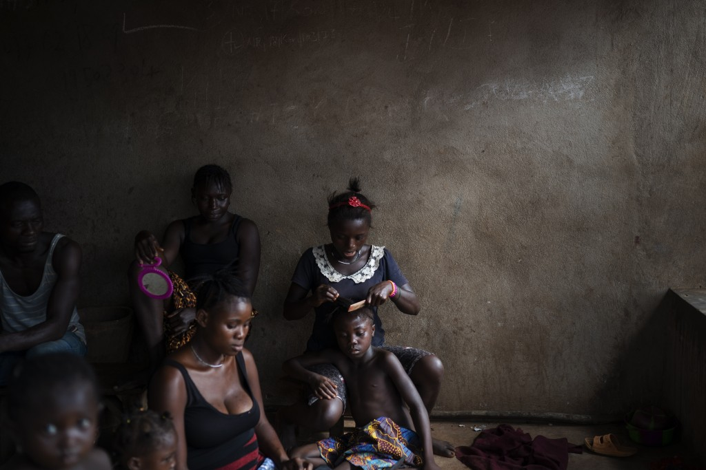 A woman combs the hair of a girl as they watch a video clip on a portable DVD player in Komao village, on the outskirts of Koidu, district of Kono, Si...