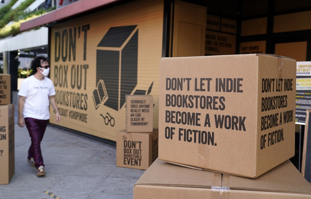 FILE - A pedestrian walks past boxes set up in front of book store Book Soup in West Hollywood, Calif., on Oct. 16, 2020, to encourage shoppers to buy...