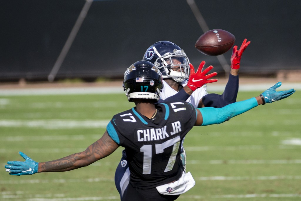 Tennessee Titans cornerback Malcolm Butler, right, intercepts a pass intended for Jacksonville Jaguars wide receiver DJ Chark Jr. (17) during the seco...