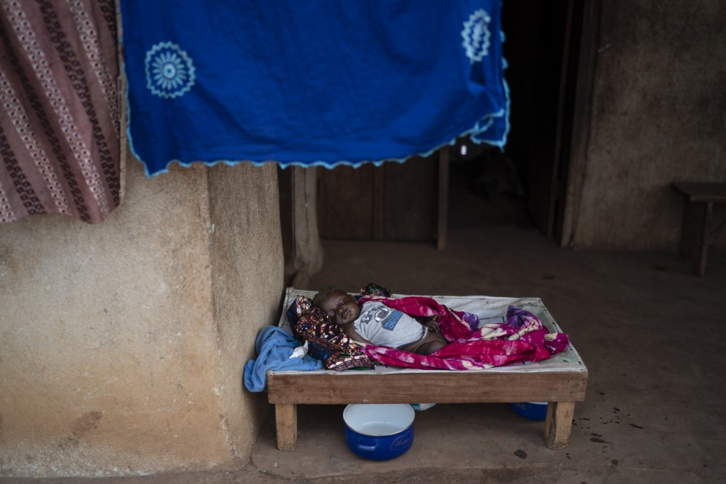A baby sleeps at the entrance of his house in Komao village, on the outskirts of Koidu, district of Kono, Sierra Leone, Sunday, Nov. 22, 2020. (AP Pho...