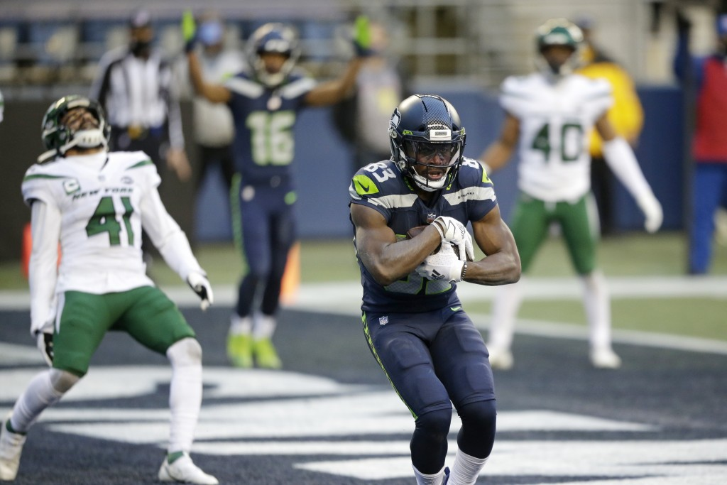 Seattle Seahawks wide receiver David Moore cradles the ball after catching a touchdown pass as New York Jets safety Matthias Farley (41) reacts behind...