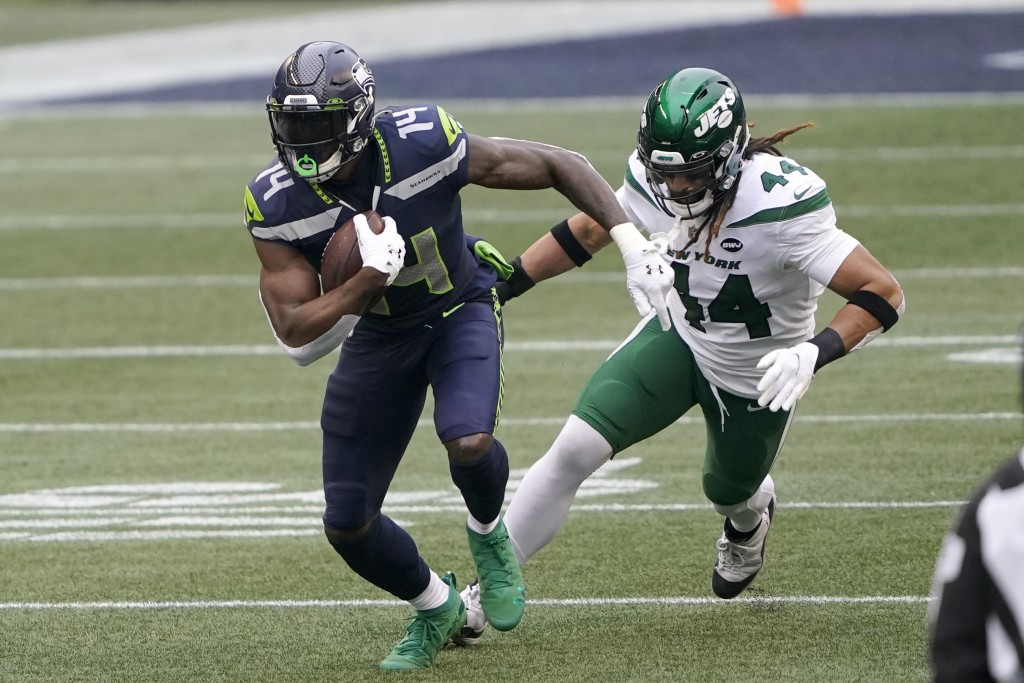 Seattle Seahawks wide receiver DK Metcalf (14) runs with the ball as New York Jets inside linebacker Harvey Langi gives chase during the first half of...