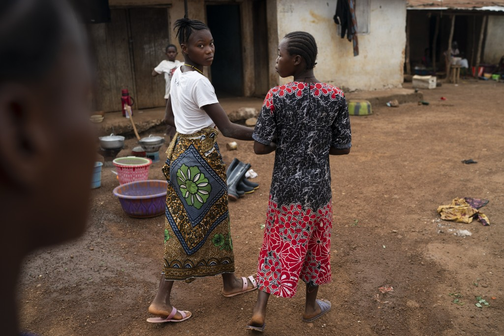 Marie walks with a friend on a street in Komao village, on the outskirts of Koidu, district of Kono, Sierra Leone, Sunday, Nov. 22, 2020. A man, in hi...