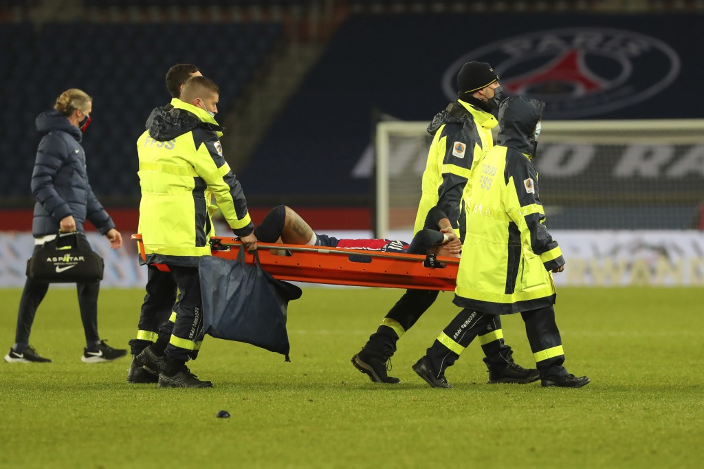 PSG's Neymar, center, is carried off the field on a stretcher after getting injured during the League One soccer match between Paris Saint Germain and...