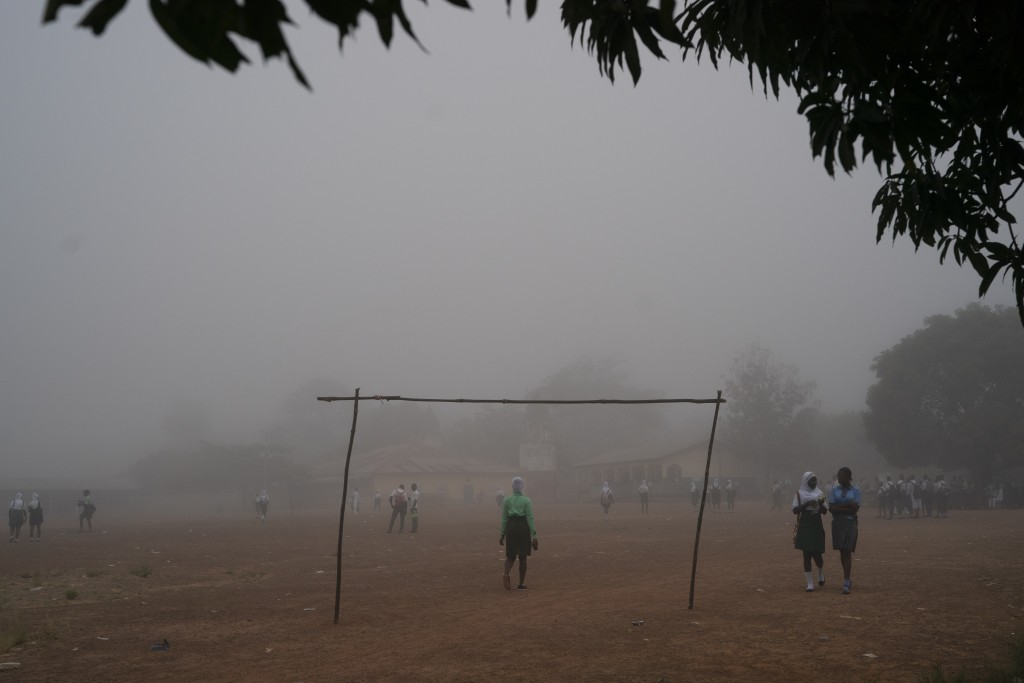 Students walks in the fog as they arrive at a secondary school in Koidu, district of Kono, Sierra Leone, Friday, Nov. 20, 2020. (AP Photo/Leo Correa)