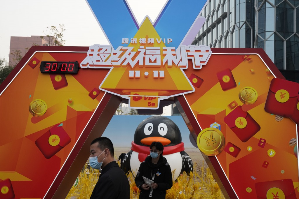 Workers wearing masks stand near a promotional booth for Tencent video in Beijing on Nov. 11, 2020. China's market regulator on Monday, Dec. 14, 2020 ...