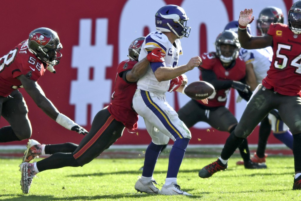 Minnesota Vikings quarterback Kirk Cousins (8) loses the football after a hit by Tampa Bay Buccaneers strong safety Antoine Winfield Jr. (31) during t...
