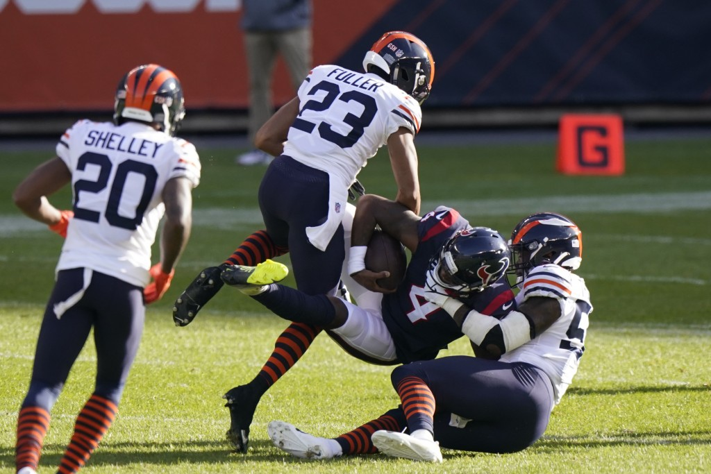 Houston Texans quarterback Deshaun Watson (4) is tackled by Chicago Bears' Kyle Fuller (23) and Danny Trevathan (59) during the first half of an NFL f...