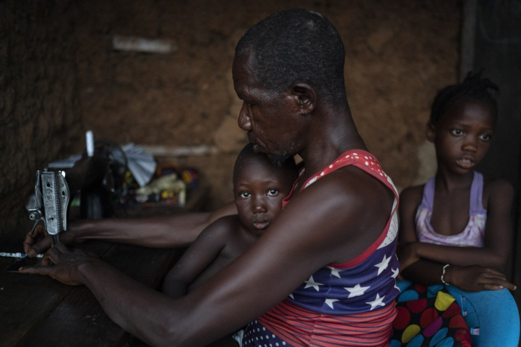 Osman works on his sewing machine as a sister of Marie stands with him in Komao village, on the outskirts of Koidu, district of Kono, Sierra Leone, Su...