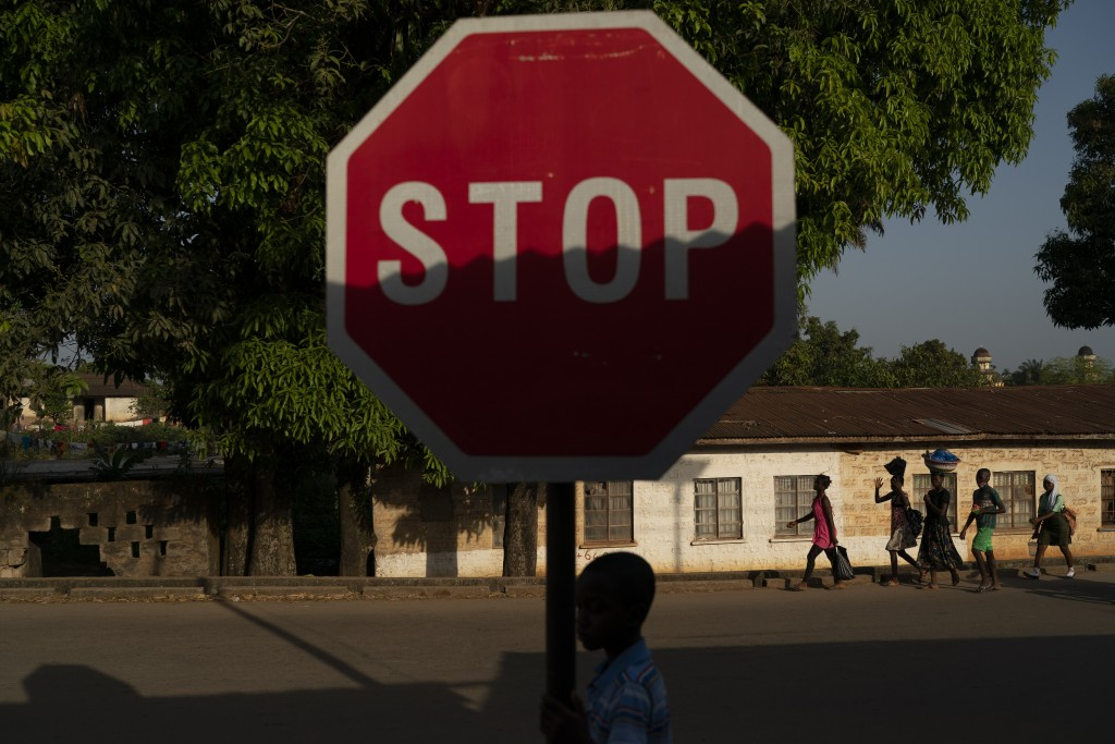 A boy walks past a stop sign in Koidu, district of Kono, Sierra Leone, Monday, Nov. 23, 2020. Only 76 coronavirus cases were confirmed in Kono distric...