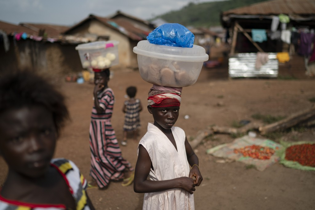 Isatu, 12, carries packets of rice flour to sell at Komao village, on the outskirts of Koidu, district of Kono, Sierra Leone, Sunday, Nov. 22, 2020. S...