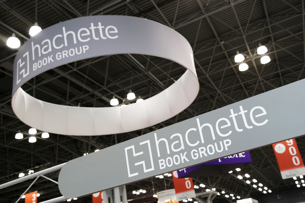 FILE - In this May 28, 2015 file photo, signs for Hachette Book Group are displayed at BookExpo America in New York. Hachette cancelled a memoir by Wo...