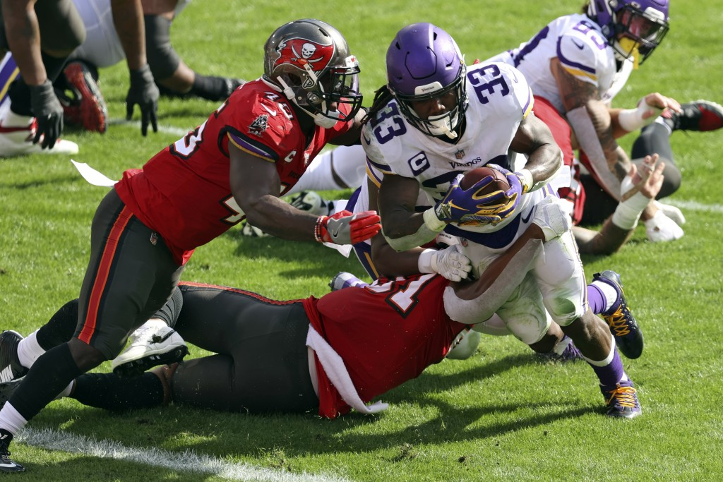 Minnesota Vikings running back Dalvin Cook (33) eludes a tackle by Tampa Bay Buccaneers inside linebacker Devin White (45) to score during the first h...