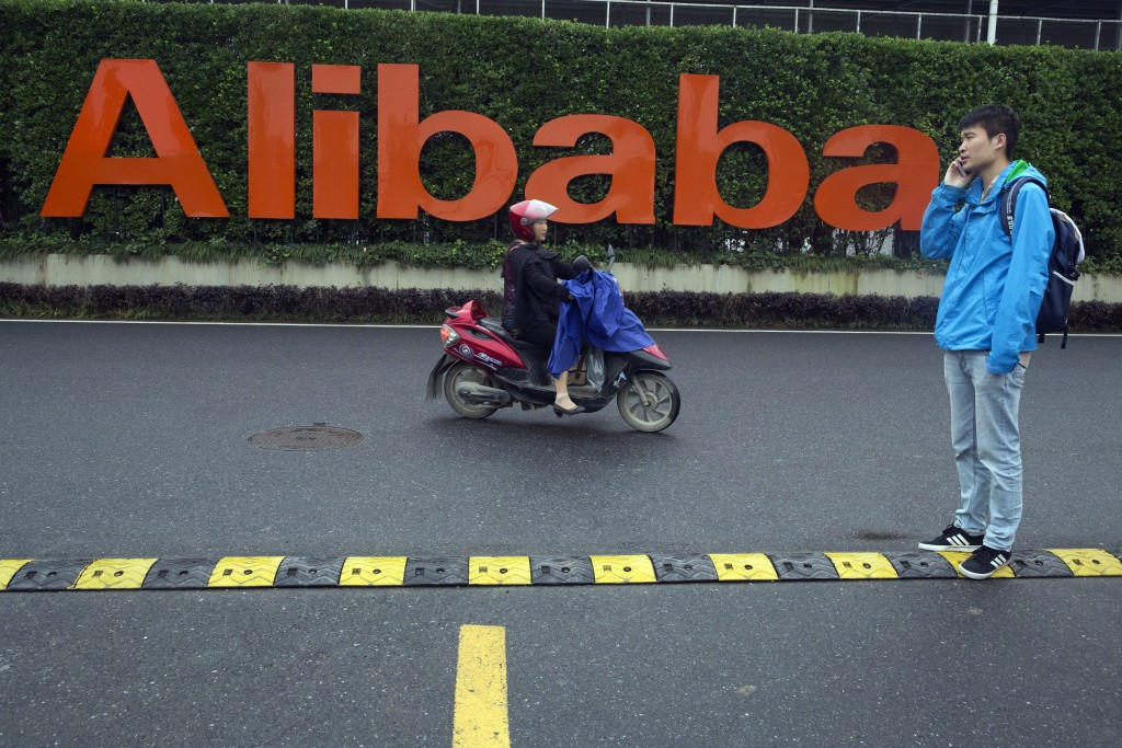 FILE - In this May 27, 2016, file photo, a man talks on his phone as a woman rides on an electric bike past a company logo at the Alibaba Group headqu...