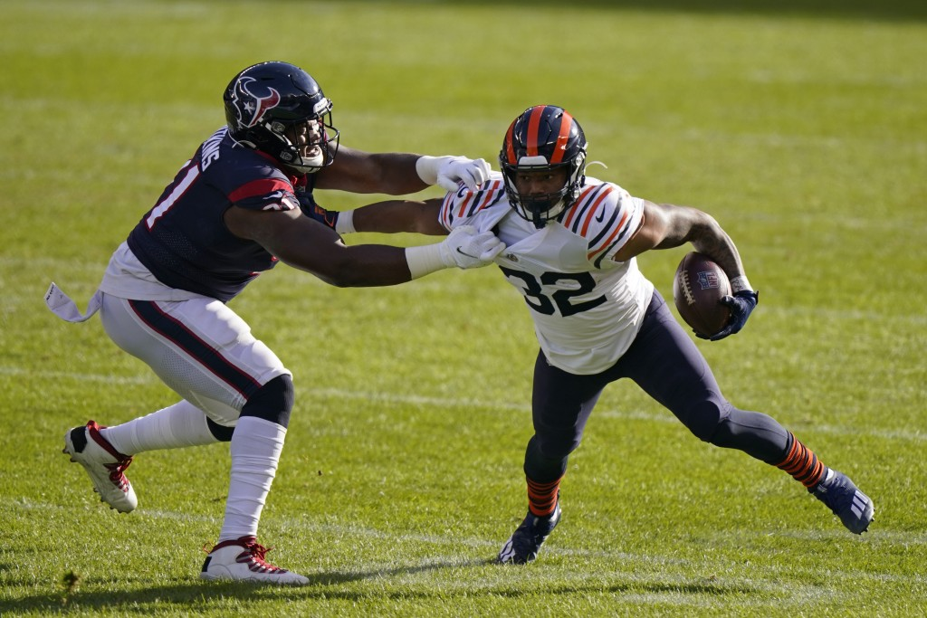 Chicago Bears' David Montgomery is tackled by Houston Texans' Carlos Watkins (91) during the first half of an NFL football game, Sunday, Dec. 13, 2020...