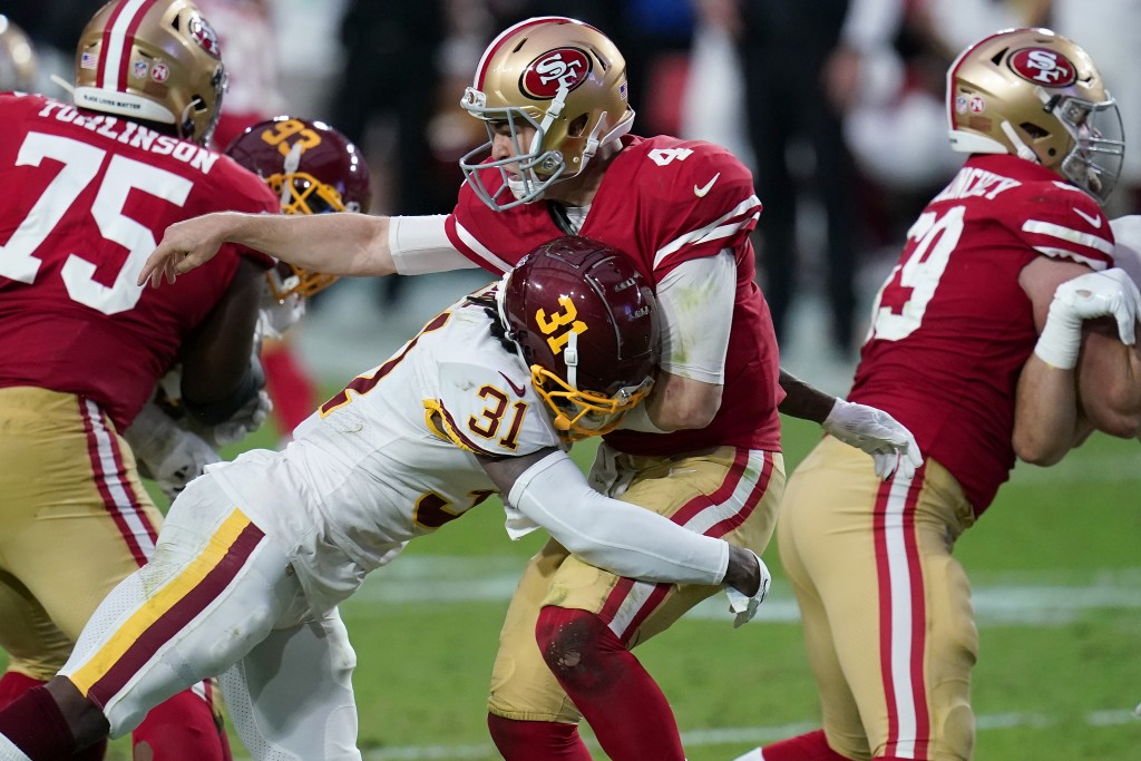 San Francisco 49ers quarterback Nick Mullens (4) takes a hit after the throw by Washington Football Team strong safety Kamren Curl (31) during the fir...