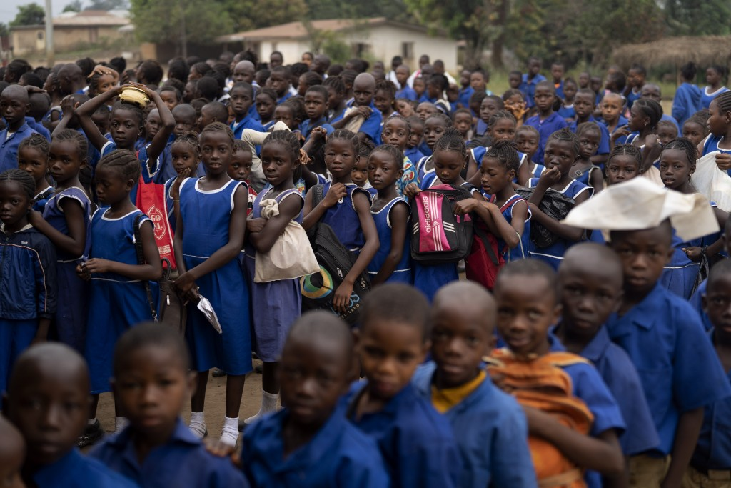 Primary students gather in line before they enter their classrooms at Kombayendeh village in Lei chiefdom, district of Kono, Sierra Leone, Friday, Nov...