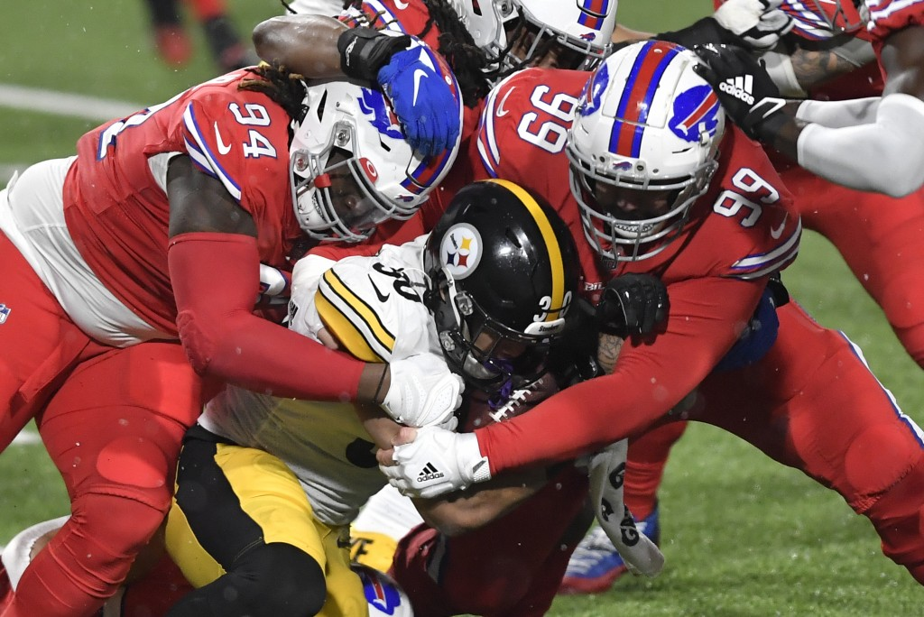 Pittsburgh Steelers running back James Conner (30) is gang tackled by Buffalo Bills defensive tackle Vernon Butler (94) and Harrison Phillips (99) dur...