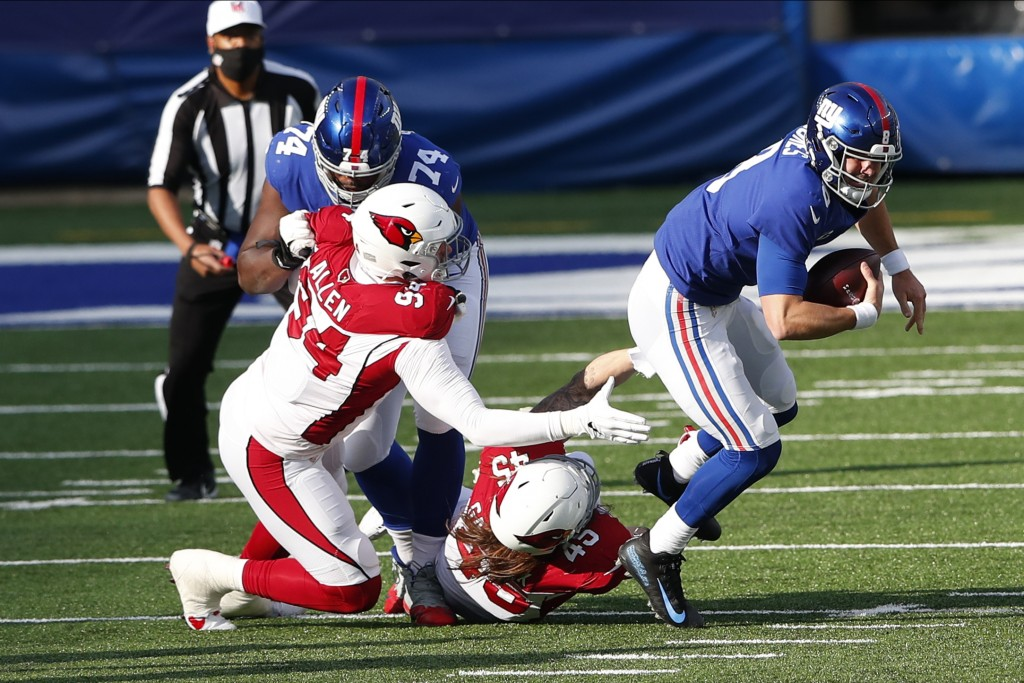 New York Giants quarterback Daniel Jones, right, is brought down by Arizona Cardinals defense during the first half of an NFL football game, Sunday, D...