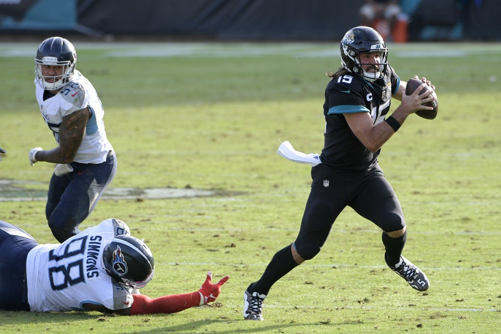 Jacksonville Jaguars quarterback Gardner Minshew II (15) scrambles away from Tennessee Titans defensive tackle Jeffery Simmons (98) during the second ...