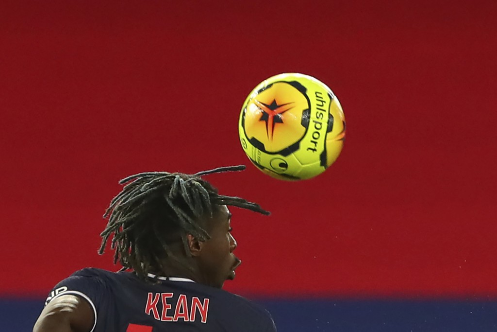 PSG's Moise Kean, second from right, heads the ball during the League One soccer match between Paris Saint Germain and Lyon, at the Parc des Princes s...