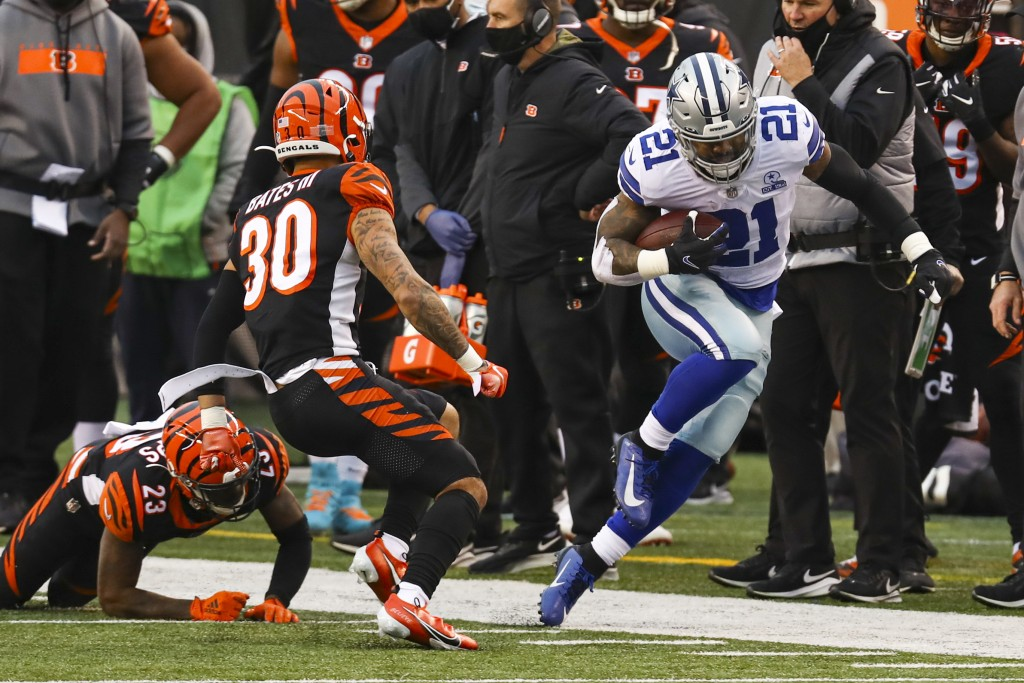 Dallas Cowboys running back Ezekiel Elliott (21) tries to stay in bounds as he's pursued by Cincinnati Bengals free safety Jessie Bates (30) in the se...