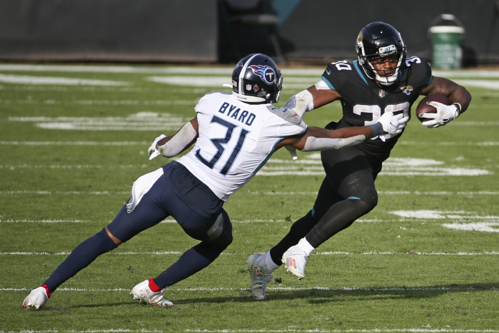 Jacksonville Jaguars running back James Robinson, right, gains yardage as he tires to get past Tennessee Titans safety Kevin Byard (31) during the sec...