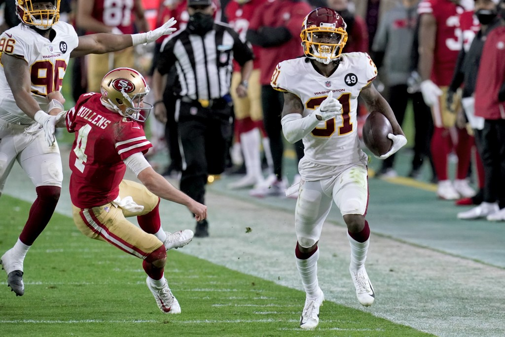 Washington Football Team strong safety Kamren Curl (31) runs back an interception for a touchdown as San Francisco 49ers quarterback Nick Mullens (4) ...