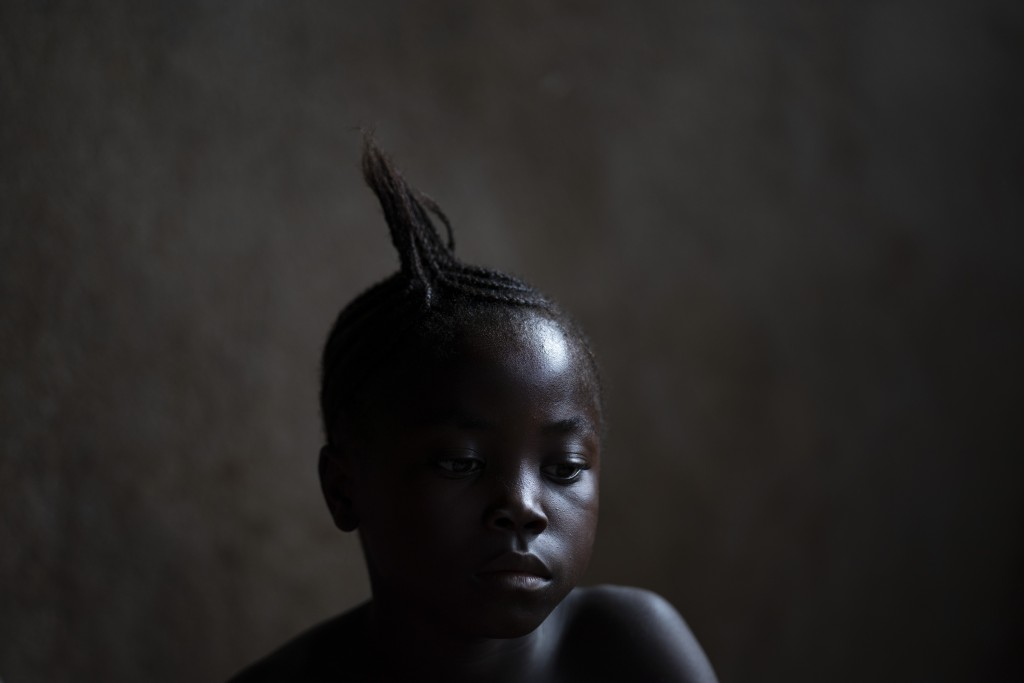 A girl watches a video clip on a portable DVD player in Komao village, outskirts of Koidu, district of Kono, Sierra Leone, Sunday, Nov. 22, 2020. (AP ...