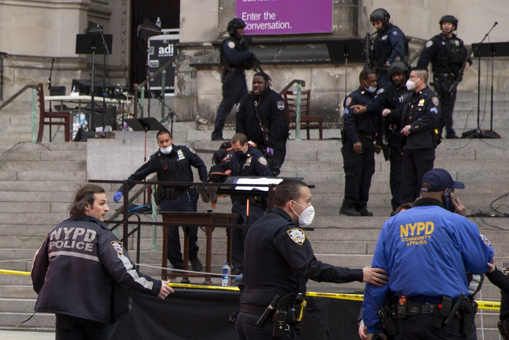 New York police officers carry a suspected gunman in a stretcher down the steps of Cathedral Church of St. John the Divine, Sunday, Dec. 13, 2020, in ...