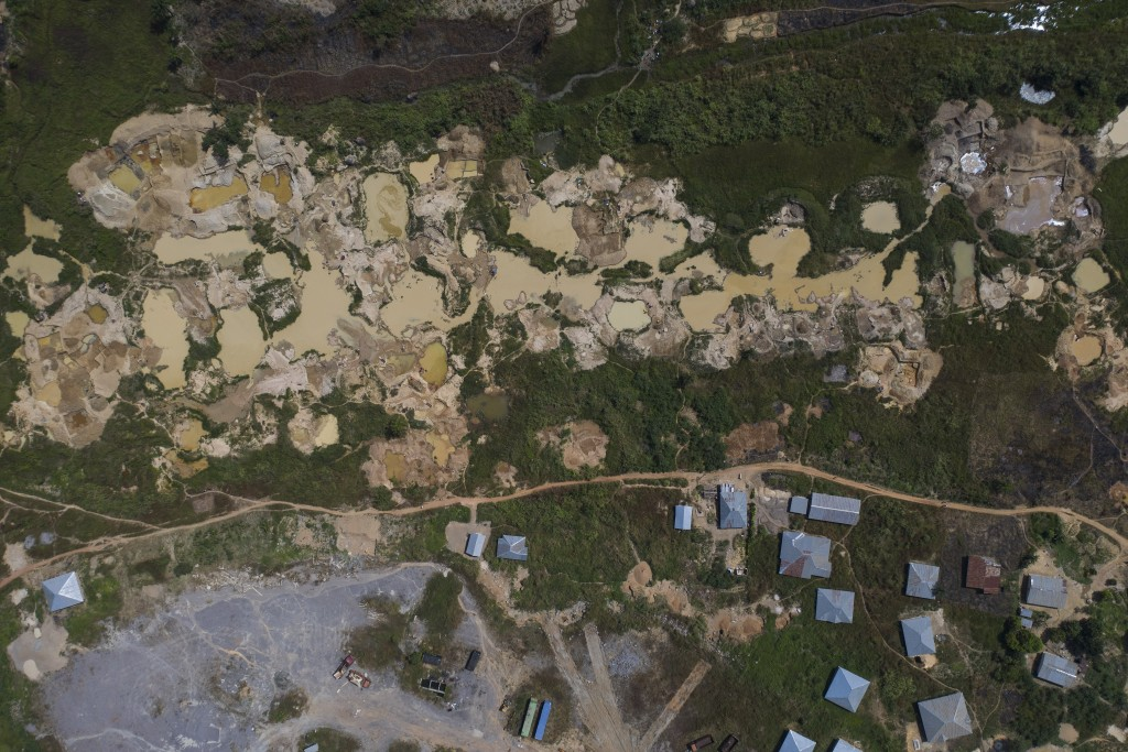 Houses stand next to a diamond mining site in Koidu, district of Kono, Sierra Leone, Sunday, Nov. 22, 2020. Mining operations have slowed with the glo...
