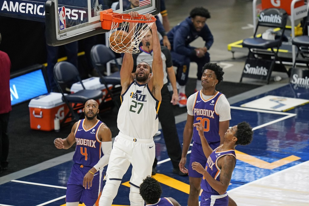 Utah Jazz center Rudy Gobert (27) dunks the ball as Phoenix Suns' Jevon Carter (4) and Damian Jones (30) look on during the second half of an NBA pres...