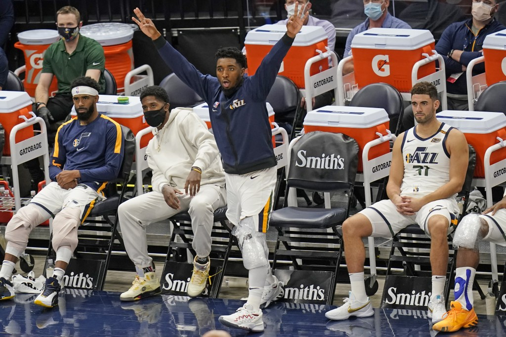 Utah Jazz guard Donovan Mitchell reacts after his teammates score against the Phoenix Suns during the second half of an NBA preseason basketball game ...