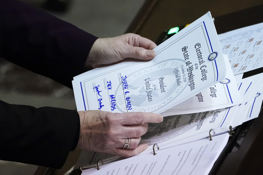Secretary of State Kim Wyman holds a ballot marked for President-elect Joe Biden that was cast by Jack Arends, a member of Washington's Electoral Coll...