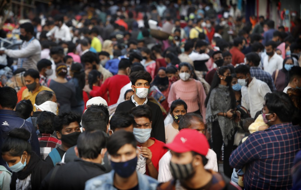 Indians wearing face masks as a precaution against the coronavirus shop at a market in New Delhi, India, Thursday, Nov. 12, 2020. With Americans, Brit...