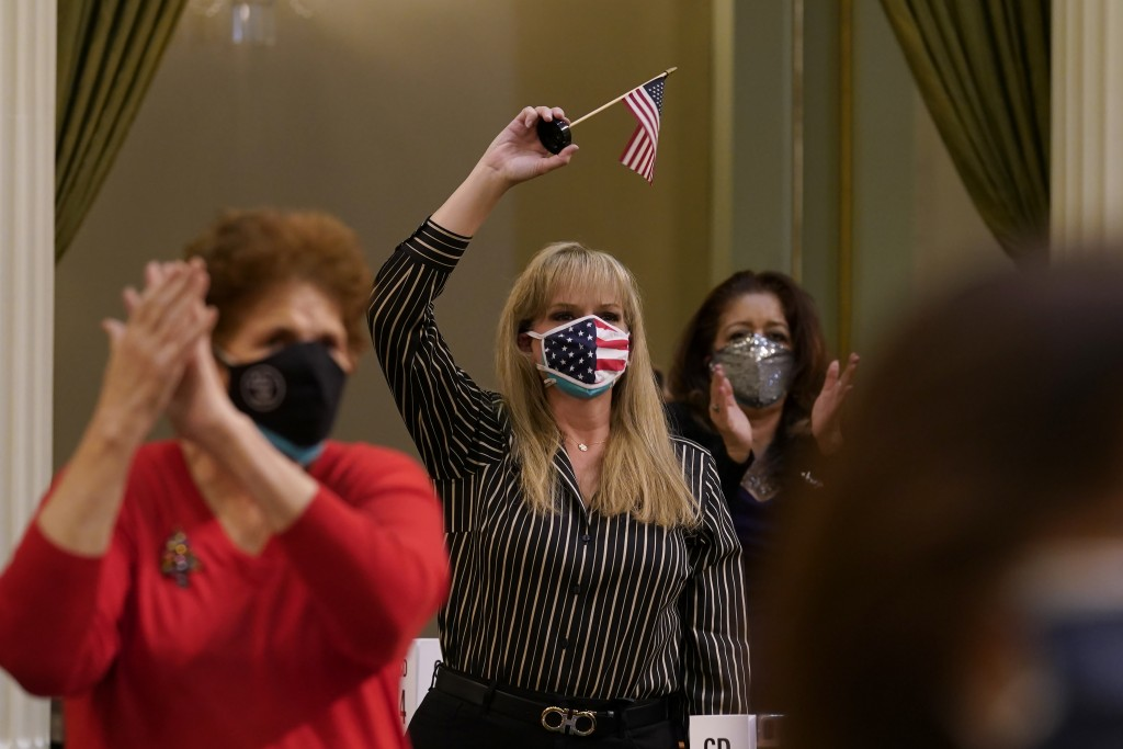 Jackie Cisneros, center, waves an American flag as she and other members of California's Electoral College celebrate the election of President-Elect J...