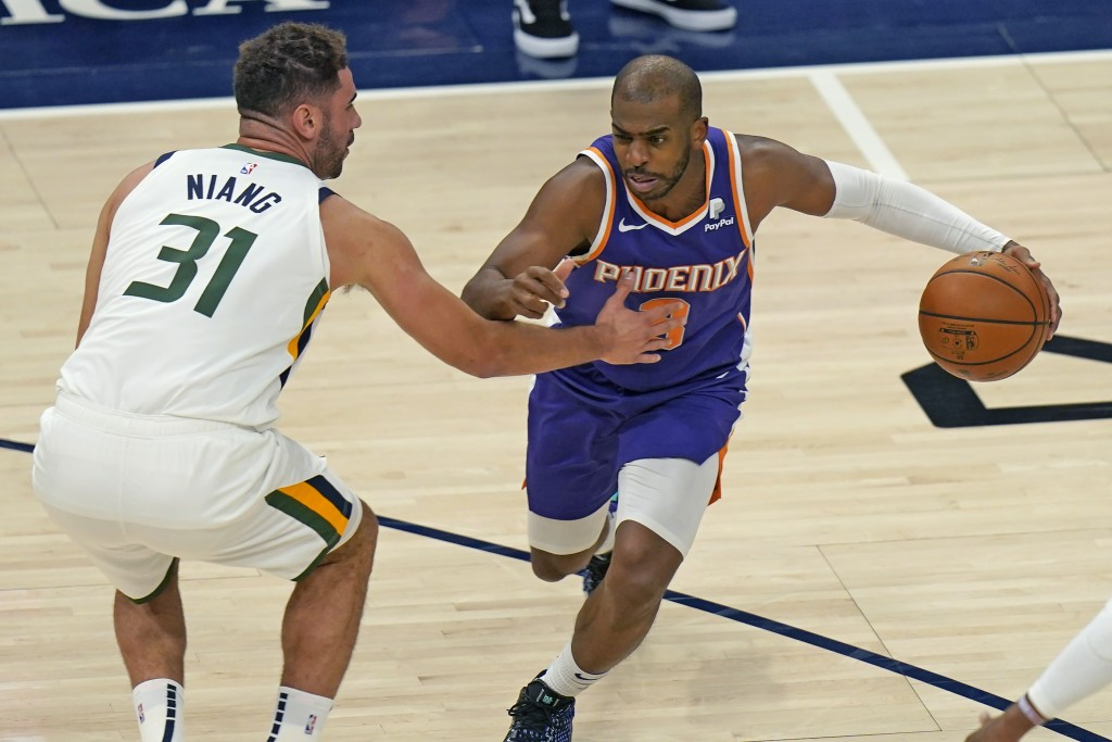 Phoenix Suns Chris Paul, right, drives as Utah Jazz forward Georges Niang, left,  defends during the first half of an NBA preseason basketball game Mo...