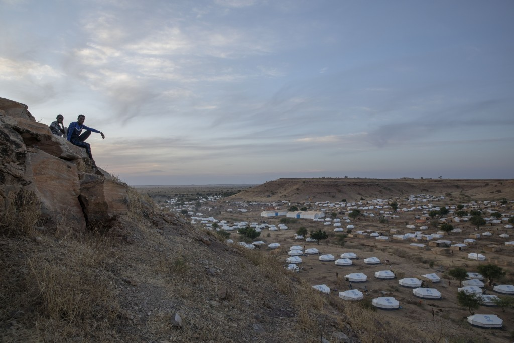Tigray men sit atop a hill overlooking part of the Umm Rakouba refugee camp, hosting people who fled the conflict in the Tigray region of Ethiopia, in...